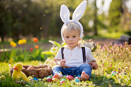 Sweet toddler boy with bunny ears, egg hunting for Easter, child and Easter day traditions. Kids and holidays