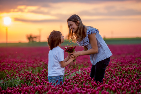 Beautiful kid and mom in spring park, flower and present. Mothers day celebration concept. Mom and son in crimson clover field, mom getting bouquet of flowers gathered from her child for Mothers day