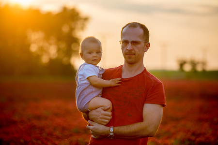Father, holding his toddler son in crimson clover field on sunset, springtime