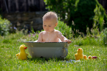 Cute little toddler boy in a basin, taking a bath in garden with bubbles and duck toys, smiling happily