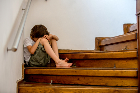 Sad child, sitting on a staircase in a big house, concept for bullying, depression stress or frustration Stockfoto