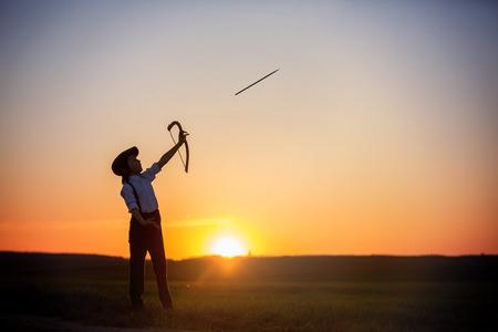 Silhouette d'enfant jouant avec un arc et des flèches, tir à l'arc tire un arc sur la cible au coucher du soleil