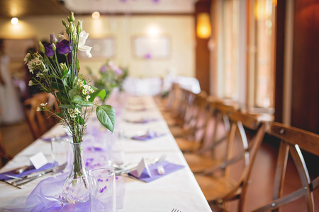Elegant table setup in purple pastels for a restaurant wedding, indoors
