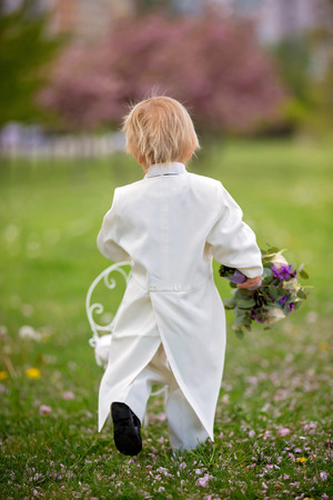 Beautiful toddler boy, dressed in white tuxedo, holding gorgeous flower bouquet for mothers day, smiling happily and giving it to mom in park