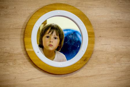 Sad little child, boy, looking through little round window of a submarine Stock Photo