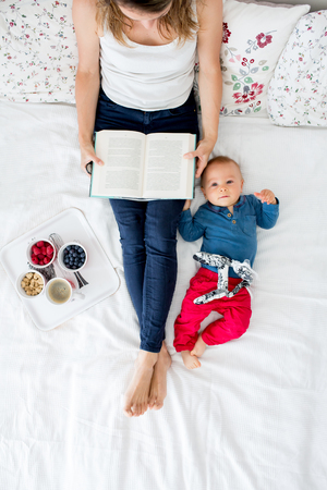 Mother and toddler baby boy, lying in bed, baby playing, mom reading a book and eating fruits, high angle shot, from above. Happy family concept
