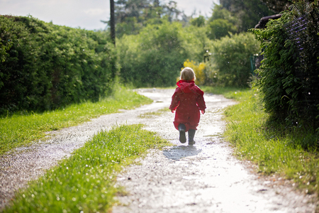 Sweet little toddler boy, blond child in red raincoat and blue boots, playing in the rain in muddy puddles, jumping and laughing with joy Foto de archivo - 124263219