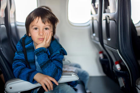 Cute preschool child, watching through window in aircraft, while traveling on vacation