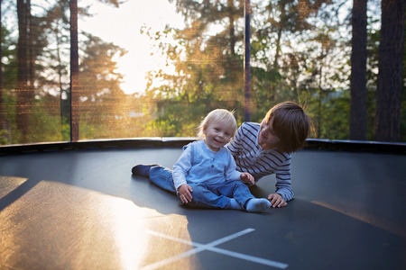 Sweet preteen boy and his toddler brother jumping on trampoline. Happy children jumping on sunset, making different shapes Banque d'images