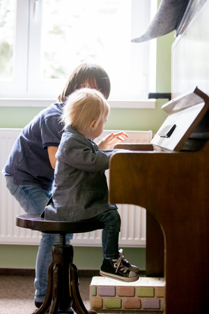 Small toddler boy enjoys playing piano for the first time, having fun
