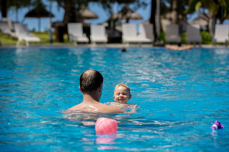 Father and son having fun in pool next to the beach in Mauritius Stock Photo