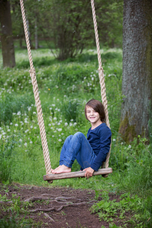 Sweet child, preteen boy, swinging on a wooden swing on a tree near dandelion field