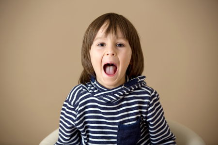 Sweet preschool boy, making faces with different emotion, isolated image 版權商用圖片