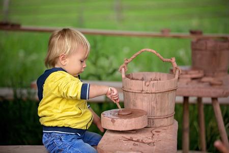 Child, cute boy, making ceramic pot on a farm