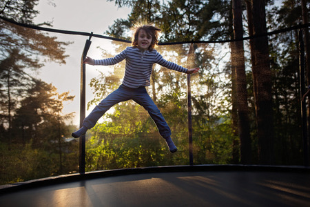 Sweet preteen boy jumping on trampoline making somersaults in the air. Child levitating. Happy child jumping on sunset