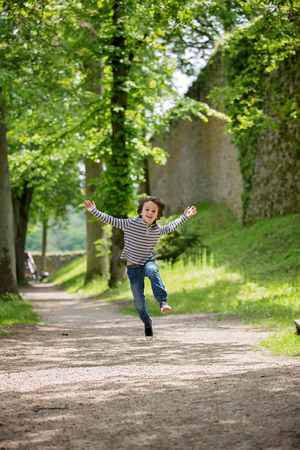 Happy Child, boy, running and jumpring on path in park with trees and stone wall Stock Photo