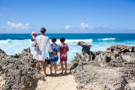 Happy children in colorful hawaiian shirts, enjoying observing the big waves on the shore of an island near Mauritius