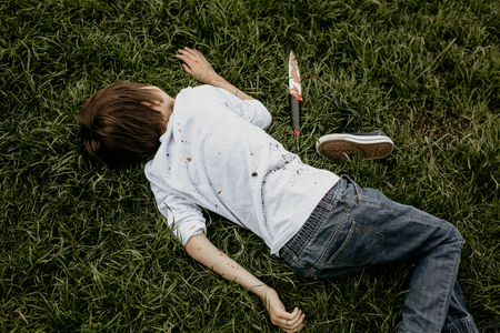 Teenager lying on the grass, covered with soil, knife next to him
