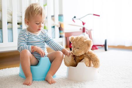 かわいい幼児の男の子、トイレトレーニング、トイレに彼のテディベアで遊んで