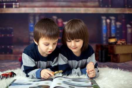 Two little children, boys, reading a book with magnifying glass at home in front of the library, lying down on the floor