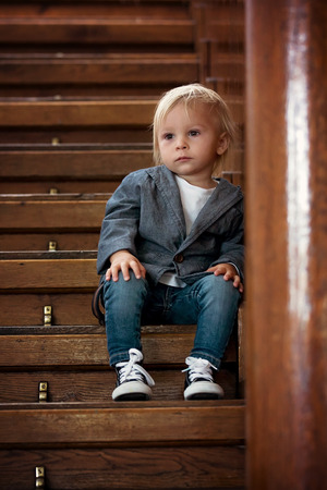 Sad child, sitting on a staircase in a big house, concept for bullying, depression stress or frustration Stock fotó