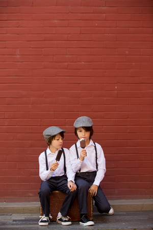 Cute children, boy brothers in vintage cloths, eating lollipop ice cream, sitting on vintage suitcase in front of a red brick wall, summertime Standard-Bild