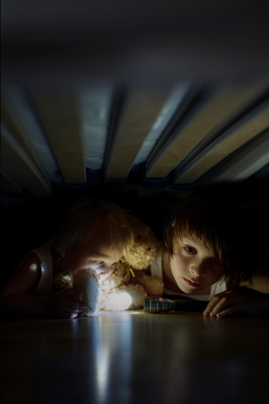 Little child, hiding under the bed, hugging teddy bear and holding flashlight, scared and sad