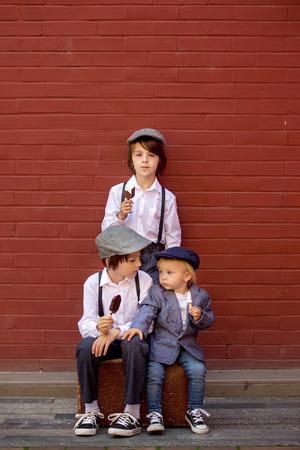Süße Kinder, junge Brüder in Vintage-Tüchern, essen Lutscher-Eis, sitzen auf Vintage-Koffer vor einer roten Backsteinmauer, Sommer Standard-Bild