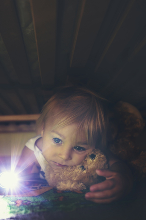 Little child, hiding under the bed, hugging teddy bear and holding flashlight, adult hand trying to reach him