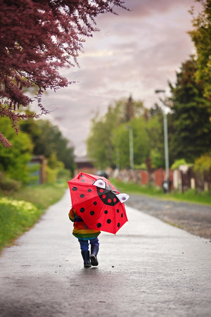 Beautiful toddler boy with rainbow raincoat, enjoying the rain in spring, holding umbrella