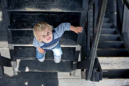 Child, toddler boy, sitting on wooden stairs, outdoor Stock Photo