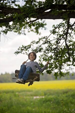 Sweet child, preteen boy, swinging on a wooden swing on a tree near oilseed field