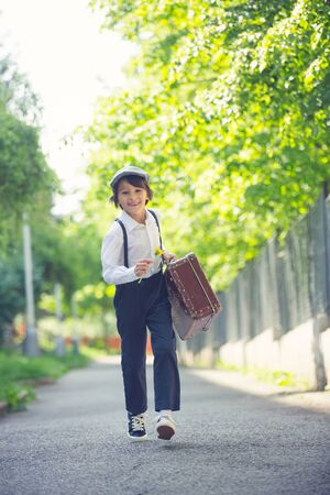 Sweet child in vintage clothing, hat, suspenders and white shirts, holding suitcase in the park, going to a holiday