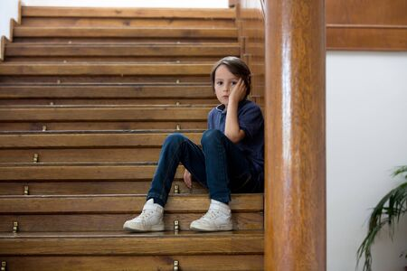 Sad child, sitting on a staircase in a big house, concept for bullying, depression stress or frustration Stock Photo