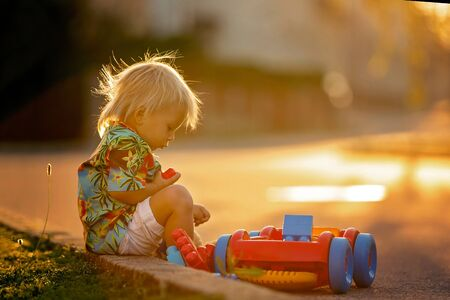 Beautiful toddler child, playing with plastic toys, blocks, cars on sunset in a small village Archivio Fotografico - 128380777