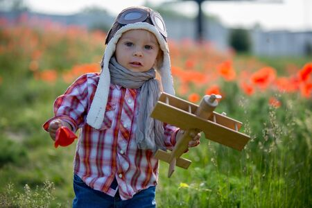 Sweet toddler baby boy, child playing with airplane in poppy fiead, beautiful sunny summer day