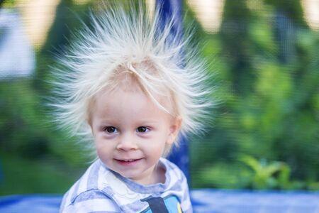 Netter kleiner Junge mit statischem elektrischem Haar, sein lustiges Porträt draußen auf einem Trampolin genommen