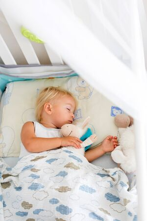 Sweet baby boy in casual clothes, sleeping in bed with teddy bear stuffed toys, summertime Stock Photo