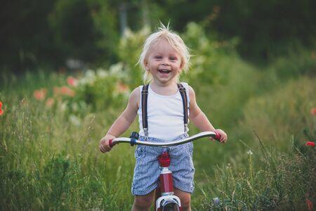 Glückliches schönes Kleinkindkind, das einen Strauß wilder Blumen hält, Retro-Dreirad im Mohnfeld bei Sonnenuntergang fährt