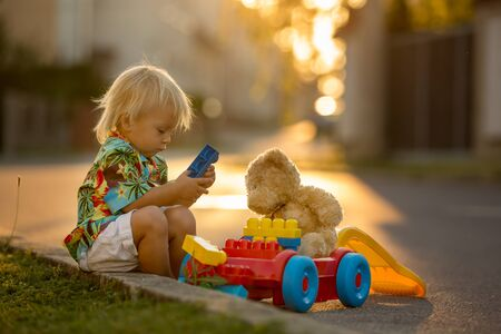 Beautiful toddler child, playing with plastic toys, blocks, cars on sunset in a small village Banque d'images - 128380896