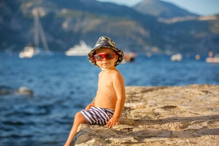 Sweet toddler boy with summer hat and sunglasses, sitting on the beach shore on sunset, enjoying the view Stock fotó