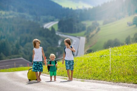 Little children, boy brothers with backpacks and suitcase, travel on the road to scenic mountains, , summertime