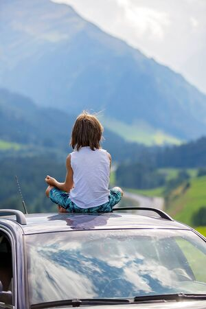 Cute child, boy sitting on a car ceiling, meditating enjoying the quietness of nature, travel on the road to scenic mountains, summertime