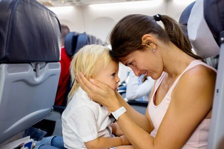 Mother and son, toddler boy, sitting together in airplane furing flight for a family holiday, mom trying to engage the child with activity Imagens
