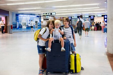 Sweet childre, brothers, boys, waking hand in hand at the airport, carrying suitcases and backpacks, family holiday