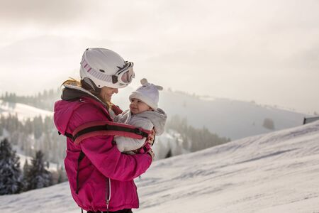 Young mother, carrying her baby boy in sling, climbing on peak wintertime, Austrian Apls, beautiful breath taking view from top of mountain
