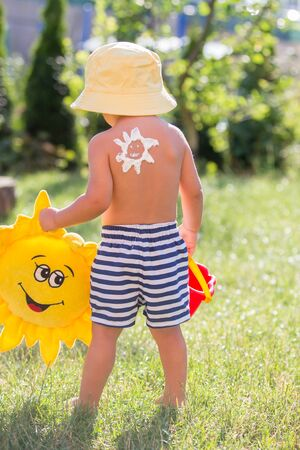 Toddler child with suntan lotion shaped as sun on his back, going at the beach with toys and flufy sun toy, walking outdoors back to camera