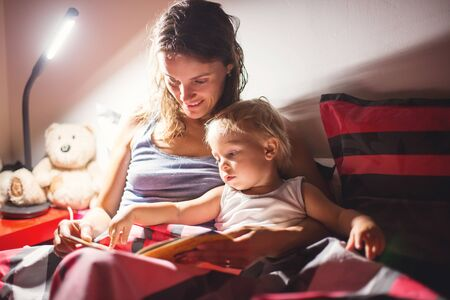 Mother, reading a book to her toddler boy at home at night, night stand lamp turned on, mom and baby hugging