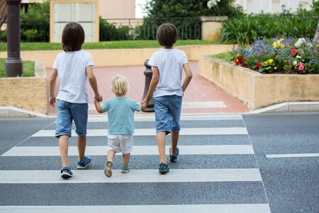 Three children, boys, brothers, holding hands and crossing a street on a striped crosswalk, checking for cars before, safety crossing the street summertime Reklamní fotografie - 128934865