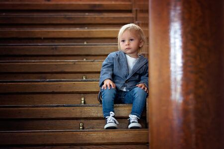 Sad child, sitting on a staircase in a big house, concept for bullying, depression stress or frustration 免版税图像
